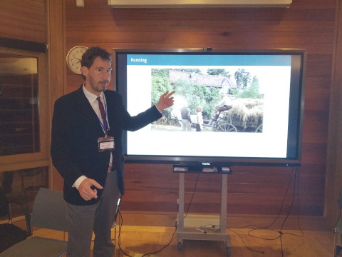 (A photo of Tristan Miller speaking at the 2nd Comedy and Artificial Intelligence Conference. Dr. Miller is standing in front of a presentation screen on which is displayed a still from a comedy film.)